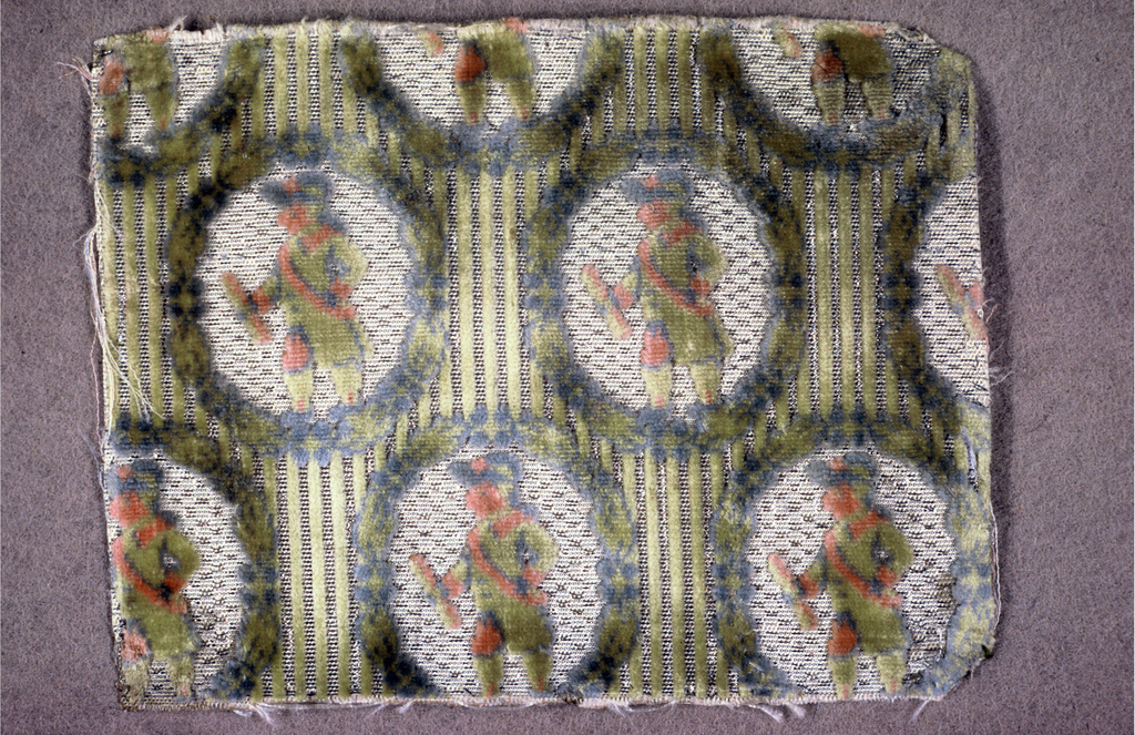 "Fragment of ""velours miniatures"" with oval flower wreaths framing a uniformed man in profile. Background has thin green cut velvet stripes that alternate with off-white stripes shot with silver threads."