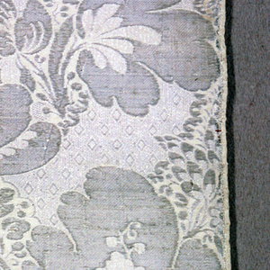 Square fragment of white silk with silver yarns showing design of large-scale symmetrical florals. Both selvages present. Edged with silver galloon.