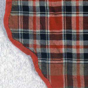 Valance fragment in a plaid pattern with a scalloped outline. Lined with plain green wool.