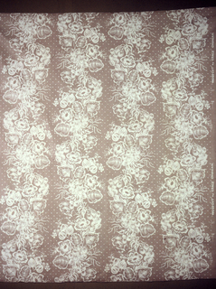 Cotton of deep cream color, screen printed in white floral design in perpendicular arrangement.