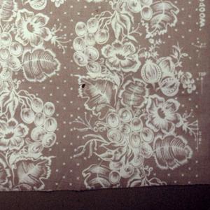 Cotton of deep cream color, screen printed in white floral design in perpendicular arrangement.