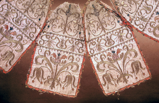 Conical shaped cover made in four sections, now partly ripped; cream white taffeta. Each section embroidered in gold thread with details in pink and green silk; stylized symmetrical flower pattern; each set edged with narrow pink fringe; lined with pink cotton.