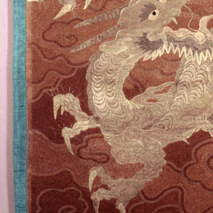Hanging of solidly couched silk in shades of brown and gray has a pattern of cloud bands and dragons before Mount Fuji.