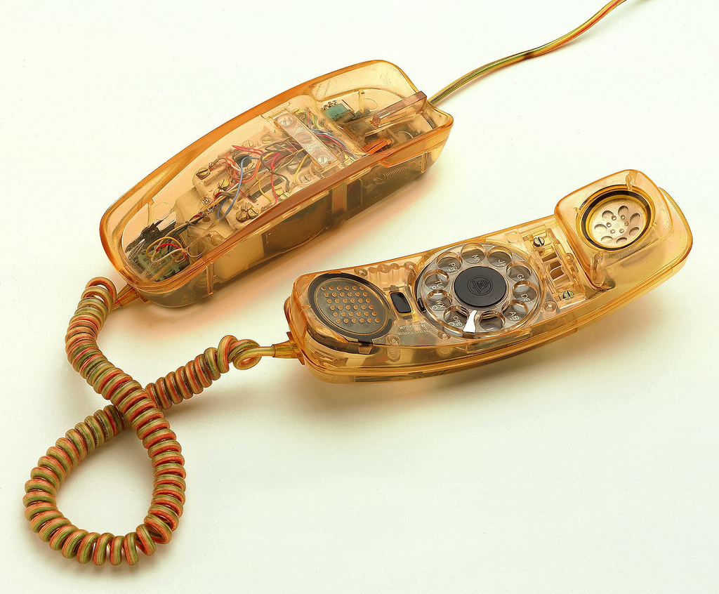 Arched rectangular body, handset with rotary dial, and coiled cord made of transparent plastic with electronic components visible.