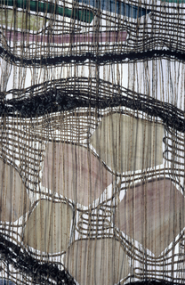 Vertical rectangle of natural hemp warp, loosely woven in colored wools, leaving much of the warp exposed. Meandering rows of rya knots in purplish wools alternate with irregularly shaped pieces of hand-colored acrylic in purples, mauves, blues, greens and yellow inserted in the weaving.