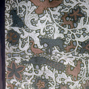 Pattern shows animals within lace-like branches.