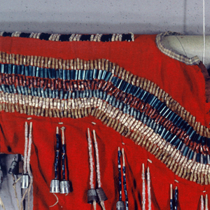 Red cotton shirt with applique bands of black, pink and gray at ends of each sleeve.  Back and front, from wrist to wrist, decorated with six rows of glass beads fastened onto leather strings, in gold, blue, red, green and white. On front, leather fringes decorated with blue and white glass beads, and finished with metal thimbles. Lined with blue and white checkered cotton. Glass beads across shoulders in alternating rows of black and white.