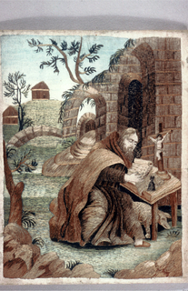 Small pictorial embroidery. Figure of a man dressed in robes, seated at a table examining scrolls; crucifix on table. Building with rougn arched doors; part of landscape beyond; sky painted blue on foundation silk. Pig under table indicates St. Anthony of Egypt. Colors in shades of light brown, grey, green and blue.