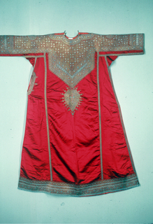 Semi-tailored dress made of pieces of red satin with flared skirt and tight-fitting sleeves. Gold and silver couched patterns closely packed cover the top of shoulders and arms, bib-like section on the front, which has one pendant, narrow border at bottom edge, and all seams. The couched yarn is either gold or silver wrapped. Note how the color of the couching yarn modifies the color of the metal wrapped yarn, which is being secured. Open pocket on the right side and braid buttons.