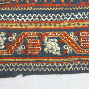 Fragment of dark blue cotton embroidered in red, yellow and white cotton in alternating striped pattern in motifs of star-shaped flower, diamond, small diamond and floral garland all in cross-stitch.