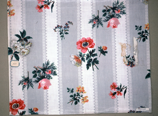 Grey ground, molette printed in pattern of checked stripes with geometric borders. Overprinted with random flower sprays – roses, poppies, pinks, and forget-me-nots, in yellow, blue, white, pink and green.