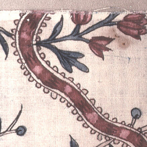 Fragment of a floral and ribbon design on white.