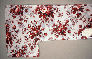 """Ground printed in grey in an elaborate foliage pattern, probably by """"molette"""". Over-printed in pattern of rose clusters in shades of brownish-red, lighter red; white areas in flowers glazed. Remains of a label, giving colors."""