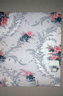 Elaborate arrangement of groudn printed by molette, in grey, with areas of white in which appear flower clusters in rose. Sweeping garlands of grey foliage frame white areas; other flower sprays and grey foliage printed over grey ground - glazed.