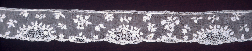 Band of Point d'Alençon worked with scattered sprays of flowers. Irregular edge of rococo design.