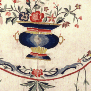 Embroidered headboard panel of ivory satin worked in multicolored silks in a pattern of delicate floral garlands, jars of flowers, ribbons and birds. Initials (illegible) embroidered in a central medallion.