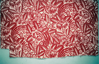Exuberant design of red flowers and leaves on a white ground. Design is a half-drop repeat. Roller was wider than the fabric.