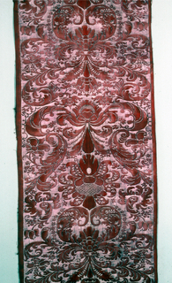 Length of printed cotton with a symmetrical design of scrolls and leaves in soft red, with color discharged in background areas.