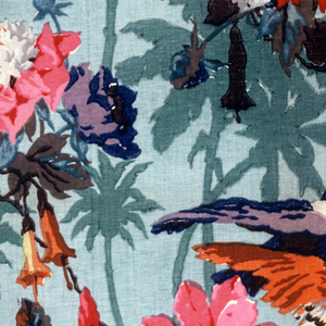 Polychrome block print on green linen visually – two layers of patterning. Back layer: green ground with darker green foliage. Top layer: serpentine branches with blue and brown branches with large polychrome flowers. Two brilliantly colored birds fly toward each other, one blue and lavender with yellow crest holds sprig of lavender berries in beak; the other is yellow with orange wings and tail, blue head and crest. Vertically repeated. Sides match at a drop repeat.