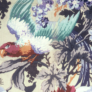 """Polychrome block print on tan linen """"cretonne"""". Serpentine grey and orange branches with grey and black leaves. Flowering garlands: two shades of dark blue, two shades of light blue, two shades of grey. Growing from branches are large maroon flowers and large lavender and orange flowers. In midst of flora is a large parrot with a maroon head, blue and green wings. Side repeat is completed by matching selvages side to side at a one-half drop repeat."""