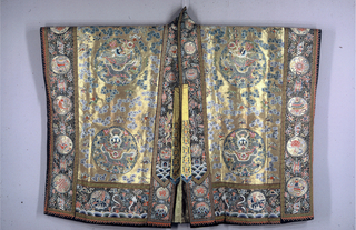 """Robe in the form of a large rectangle composed of widths of fabric which are continuous from the front hem over the shoulder to the back hem. The garment is open down the center front, and the front borders are continuous with the neck band. The borders on the outside edges are also continuous over the arm, and have openings for the hands.  Each front panel contains two medallions with a full-face dragon chasing a magic pearl in the sky above a mountain.  On the back, in the upper center is a large medallion with the """"sacred Pagoda"""" (Lamaist) plus two small medallions, one with a representation of the sun, the other the moon. Below are two large medallions each with a profile dragon chasing a magic pearl in the sky above a mountain. These three large medallions on the back are placed above mountains raising out of a foaming sea. The entire field of the front and back panels is filled with clouds, auspicious symbols, and bats carring symbols. The background is metallic gold with the pattern in colored silks. The vertical borders on the front and back contain medallions with the 8 Buddhist Emblems in colors on a black background. The bottom bands on front and back have dragons raising out of the sea, medallions containing either a carp, turtle with snake, or Ch'i-lins, plus other auspicious symbols in colors on a black background.  Many of the popular and commonly used Chinese symbols are used including the 8 Buddhist emblems, those of the Taoist Immortals, 12 Imperial, and 100 Antiques.  The entire pattern is embroidered, as is the background on the front and back panels (the background of the borders and bands is the foundation fabric). The entire robe is lined with silk 8-harness satin damask with an all-over pattern of clouds (Ming type) in greenish-yellow and tan. There are two embroidered yellow silk pointed tabs and one button with loop on the edge of the opening."""