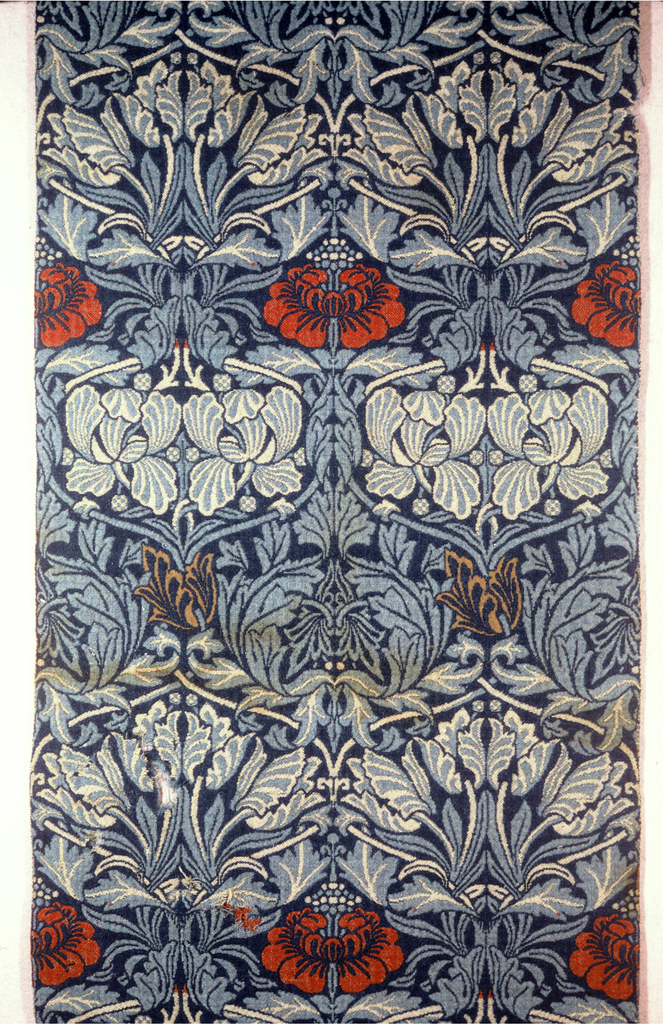 Eight pieces sewn together to make a panel; six are full loomed widths. Ogival lattice of vine and leaves framing tulips and roses. In light blue and ivory on a dark blue ground, with some flowers in red and orange, in alternating rows.