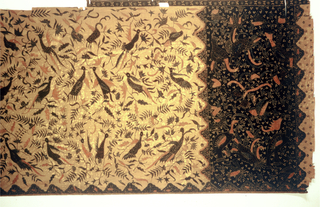 Portion of a sarong with pattern of birds and flowers in pale red and two shades of blue on yellow ochre ground in the the body or 'badan'. Somewhat similar pattern in larger scale is printed in the same colors on the the head or 'kepala', a wide strip dyed black over the base ochre color. Batiked and patterned on one side only.
