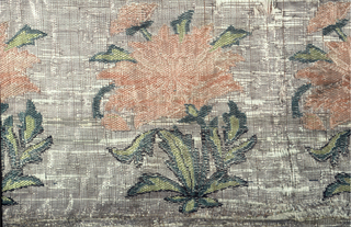 Panel with rows of flowering plants facing alternate directions in each row in shades of orange and green on a silver ground. Fragment is enclosed on all sides by four woven strips applied as borders, all patterned by flowering plants on worn metallic ground. In each corner is a triangular-shaped fragment with rows of small flowering plants on a metallic ground. Guard stripes of silk taffeta in vermillion, purple, light purple, and light blue-green.