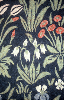Allover pattern of twelve kinds of plants with flowers in green, blue, ivory and red on a dark blue ground. Hanging is lined with dark blue cotton.