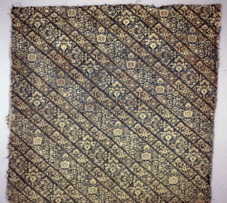 Blue-green embroidery on an ivory ground showing diagonal floral bands. Type of material used for women's pants.