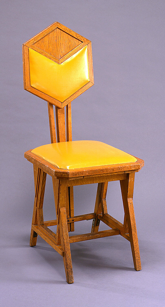 Side chair with octagonal seat, hexagonal back supported by three central vertical members which rise from seat stretcher. Legs attached at slanting angles to form triangular voids and solids and irregular hexagonal voids at intersections with stretchers. Slip seat and back panel covered in yellow leatherette.