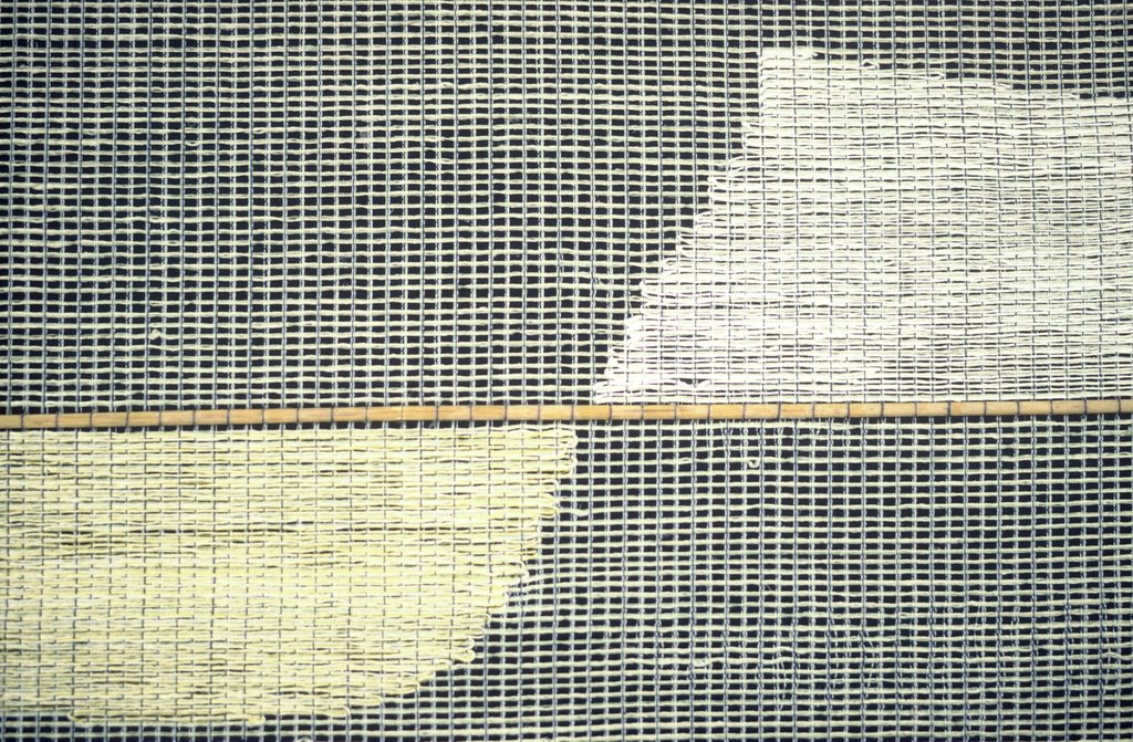 Woven hanging with a dark gray band on each side and at the bottom giving the illusion of depth. Irregular rectangles in graduated sizes appear tangent to horizontal reeds inserted every few inches. The entire hanging is semi-transparent in shades of light grey, pale yellow and pale pink.