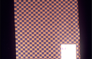 Small checkerboard pattern woven in navy and tan. Cut on all four sides.