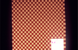 Small checkerboard pattern woven in dark red and yellow/tan. Cut on all four sides.