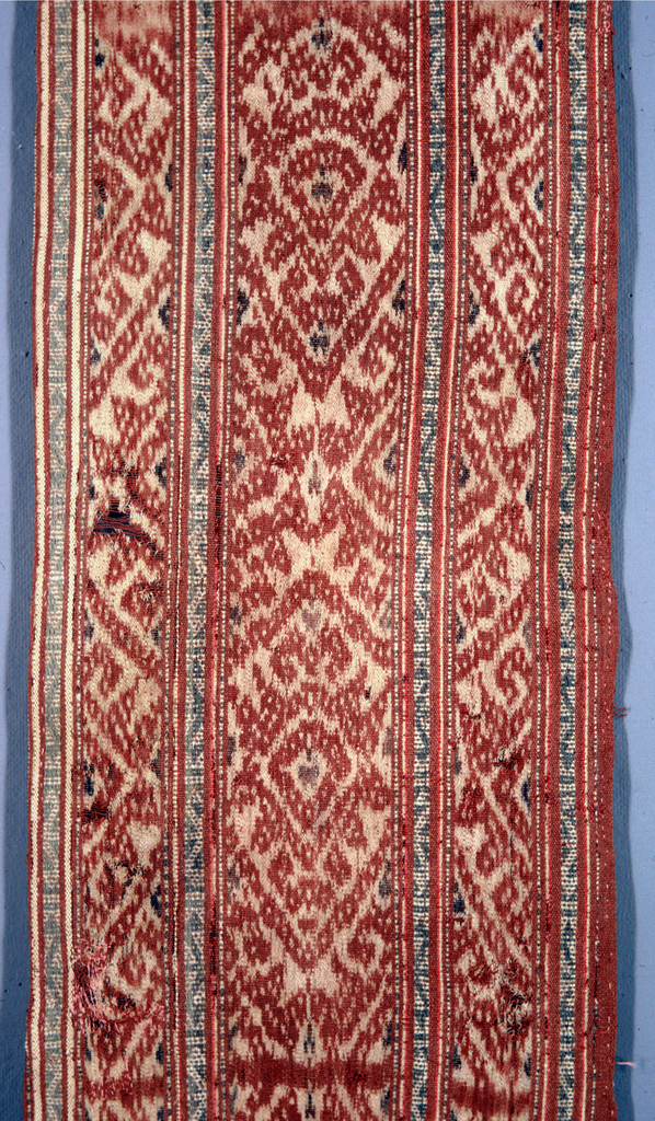 Long narrow strip of fabric divided into three (warp) stripes, each patterned by ikat in ivory, rust-red, and black with geometric shapes--sections form an all-over diamond pattern. The three stripes are separated from each other by a narrow blue and ivory stripe patterned by a repeat of small hooks.