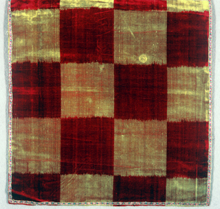 Small piece of woven velvet with a checkerboard pattern of alternating deep red and gold squares.