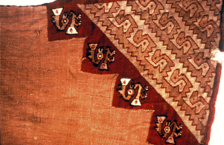 end of a loin cloth with triangular-shaped woven area at one corner: interlocked birds in two shades of light brown outlined with red forming a triangular-shaped all-over patterned area which is framed in red. the wide stepped edge on the inside contains birds, each with head ornaments, in shades of brown and yellow with black outlines.