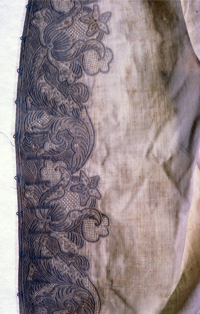 Long white sleeveless vest heavily embroidered along the front and bottom with areas of quilting, drawnwork and knots, through two layers of fabrics. Floral design with heavy leaf scrolls.