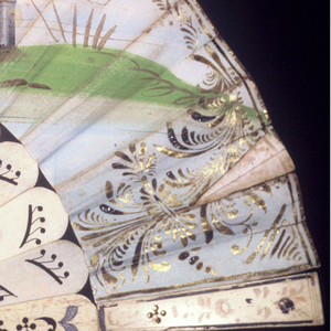 Pleated fan. Printed and hand-colored paper leaf. Obverse:  a Turkish scene showing a seated man reclining with with women, servants and musicians. Reverse: a Renaissance scene showing bobbin lace making and spinning. Drilled and painted bone sticks with metallic foil. Mirror on one guard. Mother-of-pearl washer at rivet and gilt metal bail.
