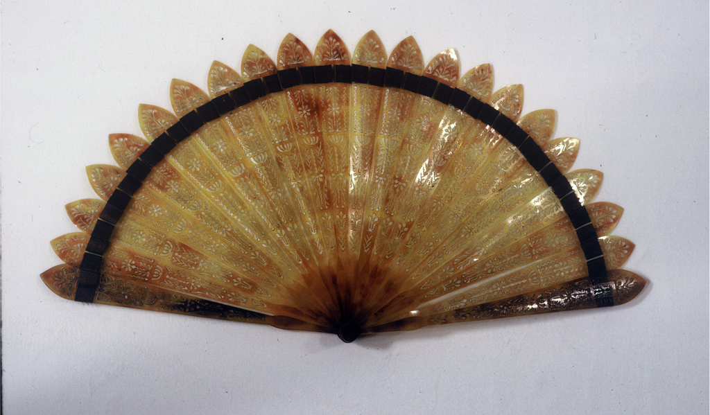 Brisé fan. Pierced tortoise shell sticks with brown silk connecting ribbon.