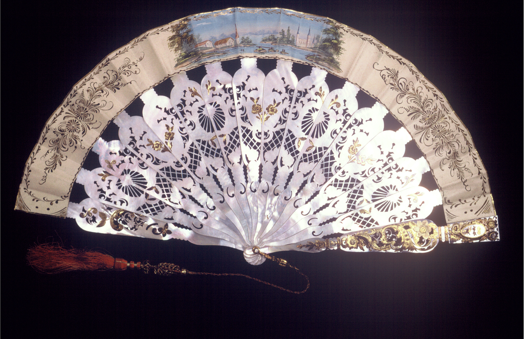 Pleated fan with double leaf. Obverse: a narrow printed and hand-colored paper leaf showing a pastoral scene. Reverse: a painted parchment leaf showing a coastal scene. Elaborately pierced and gilded mother-of-pearl sticks. Rivet set with clear faceted stone and gilt metal bail. Tassel of silk and metal threads.