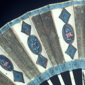 Pleated fan. Front leaf of die cut and painted paper showing oval and diamond-shaped panels, back leaf of die cut paper. Sticks of ivory with applied metallic foil.