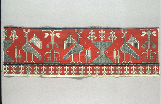 Embroidery in dark red silk forms the background with the design outlined in back silk reserved on the plain weave foundation cloth. repeating motifs of two birds facing an hour-glass shape with stylized plants on top alternating with a plant form at the bottom of which are two small animals facing each other. Small birds face the large birds. Border of elaborate plants.