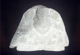 Woman's cap in natural linen showing symmetrical flowers.
