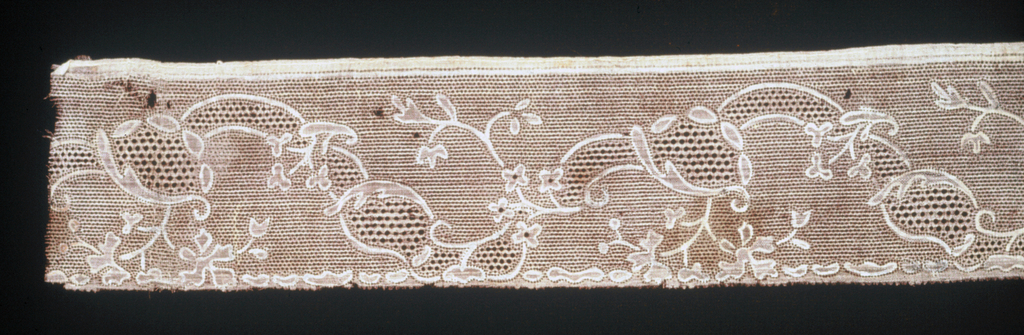 Fragment of band with a design of a scrolling vine and flowers made by punching a painted pattern on a silk fabric.