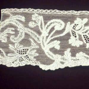Fragment with a scrolling vine and flower design. Some scrolling lines have a stiff quality.