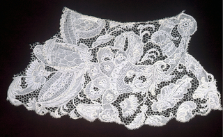 """Fragment with """"bizarre-style"""" patterning including a cornucopia overflowing with large exotic floral forms. Variations on the buttonhole stitch create discrete pattern areas. Various parts of the design have a raised cordonnet, and pattern areas are connected by a hexagonal mesh with picots."""