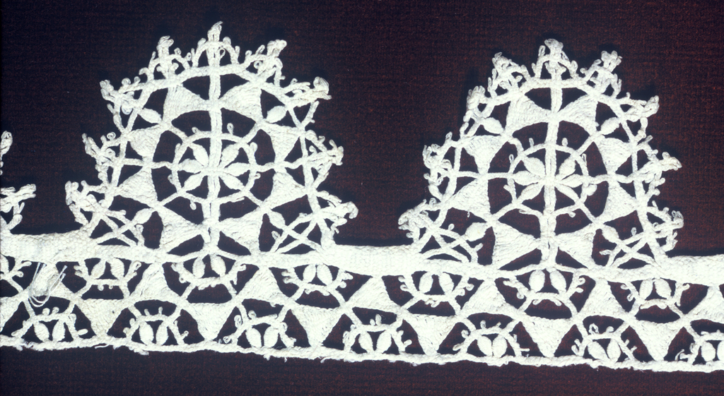 Band fragment with an oval tab edge in a geometric floral pattern. Design is taken from needle lace.
