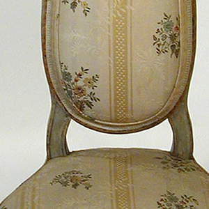 Slender, lyre-shaped back on curved molded supports; exposed frame painted gray; bow-shaped arm rest; low rounded seat with exposed frame with simple molding; quatrefoil rosette in square above each short fluted forleg and above side of each sharply slanting fluted rear leg; small square within square above back of each rear leg; peg-top feet.  Back, seat and arm rest upholstered in modern ivory silk with yellow stripe and multi-color bouquets.