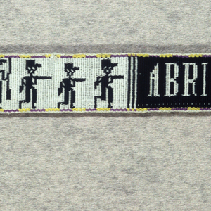 Narrow black and white belt with figures carrying guns, plants and geometric shapes; yellow and blue border.